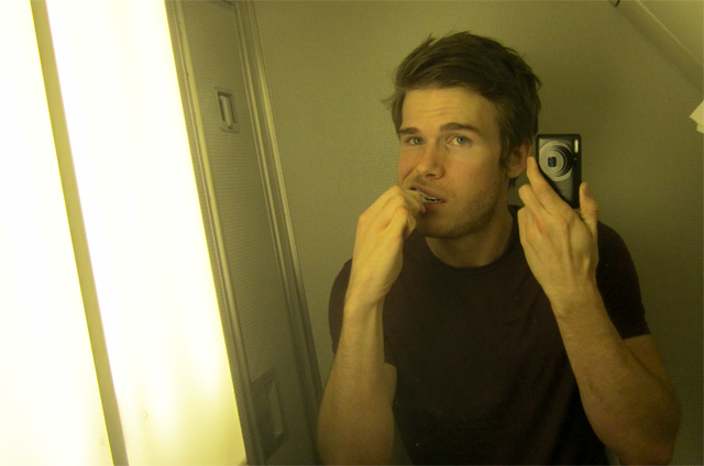 Colin Wright brushing teeth in airplane bathroom