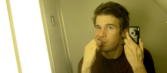 Colin brushing his teeth in an airplane bathroom
